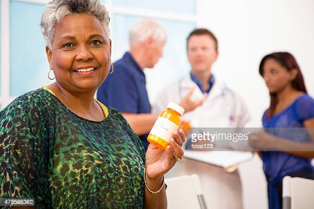 Happy senior woman holds prescription medication. Doctor, patients background.