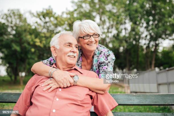 happy senior woman hugging her husband sitting on the bench in the park - retirement community stock pictures, royalty-free photos & images