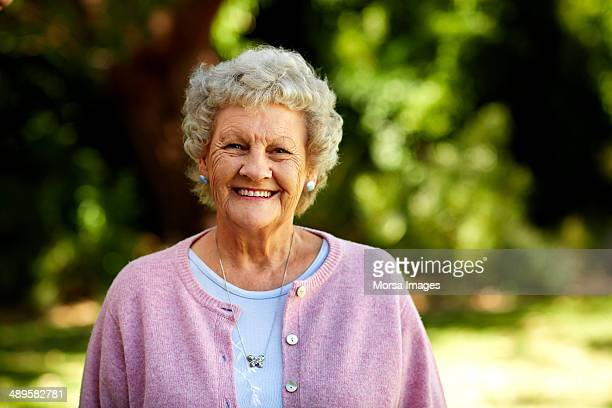 happy senior woman in park - cardigan sweater stock pictures, royalty-free photos & images