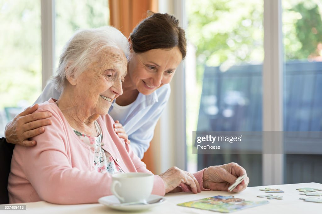 Happy senior woman in wheelchair with caregiver : Stock Photo