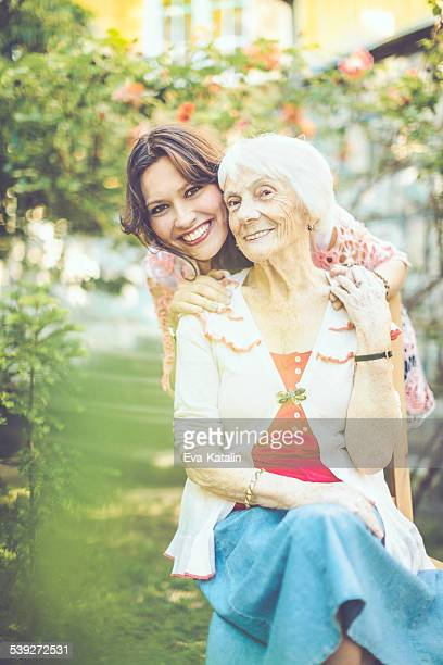 Happy senior woman is embraced by her trustful granddaughter