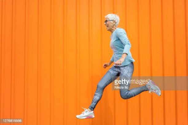 donna anziana felice che salta su sfondo arancione. - saltare foto e immagini stock