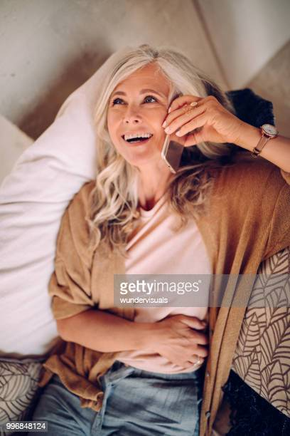 happy senior woman laughing while talking on mobile phone - one mature woman only stock pictures, royalty-free photos & images