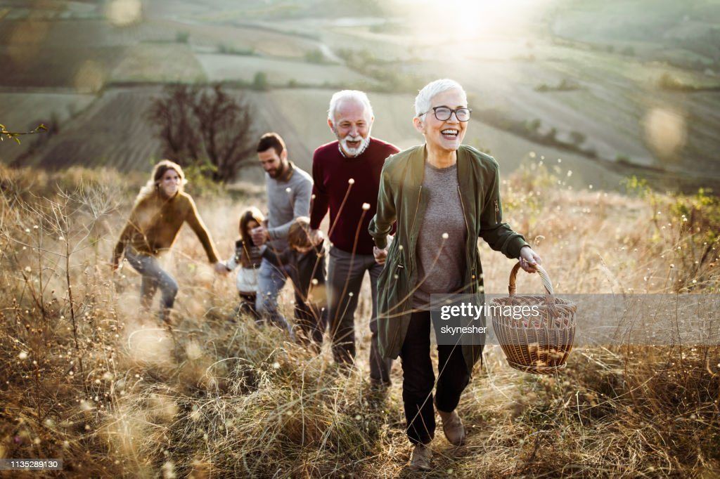 Happy senior woman leading her family to perfect picnic place on the hill. : Stock Photo
