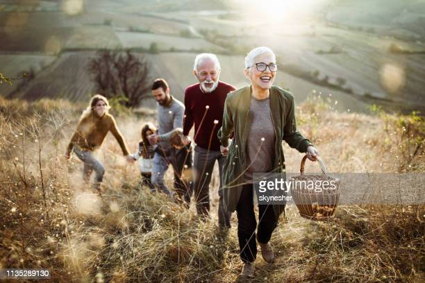 happy senior woman leading her family to perfect picnic place on the hill. - felicità foto e immagini stock