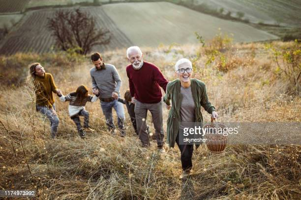 happy senior woman leading her family to perfect picnic place on the hill. - picnic stock pictures, royalty-free photos & images