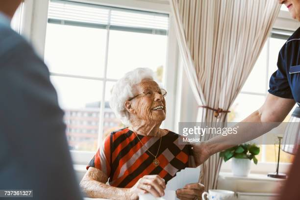 Happy senior woman looking at caretaker while playing cards with family