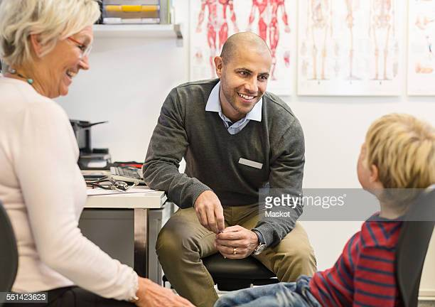 Happy senior woman looking at grandson talking to doctor at orthopedic clinic
