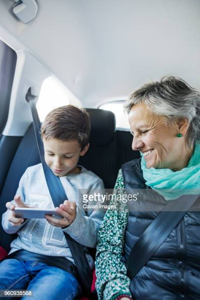 Happy senior woman looking at grandson using smart phone in car