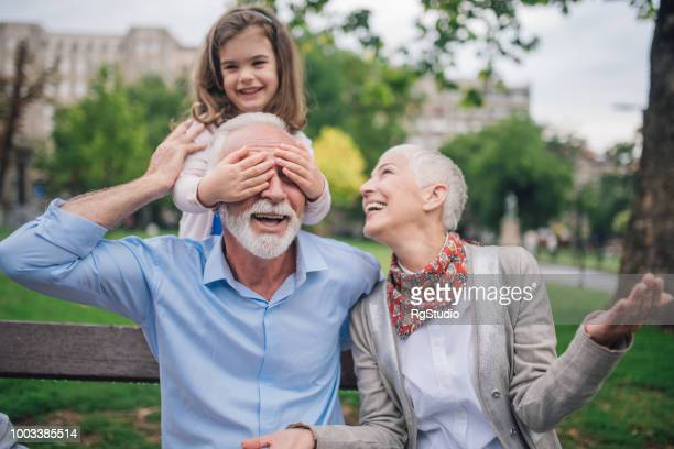 happy senior woman looking at young child covering her husband's eyes - hands covering eyes stock pictures, royalty-free photos & images