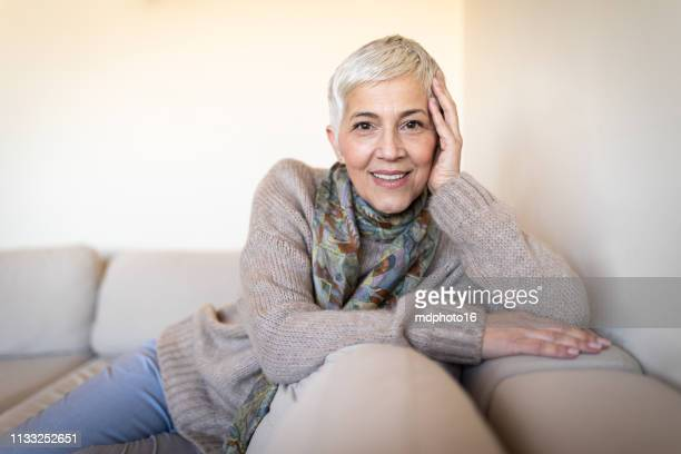 happy senior woman on couch - dentures stock pictures, royalty-free photos & images