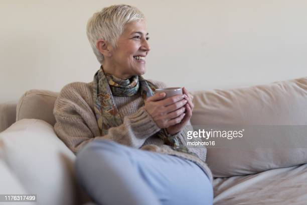 happy senior woman on couch - tranquil scene stock pictures, royalty-free photos & images