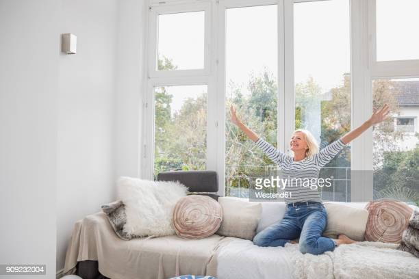 happy senior woman on her couch in the living room - arme hoch stock-fotos und bilder