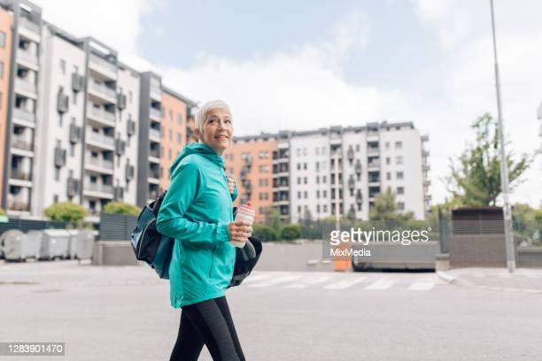 トレーニングクラスに行く途中の幸せな先輩女性 - スポーツバッグ ストックフォトと画像