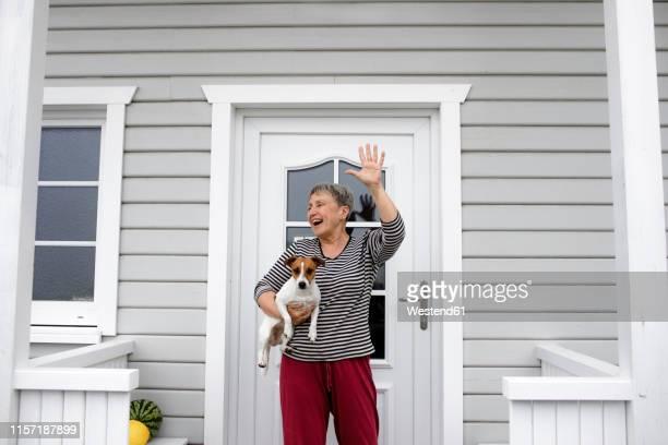 happy senior woman on porch with her dog raising her hand - winken stock-fotos und bilder