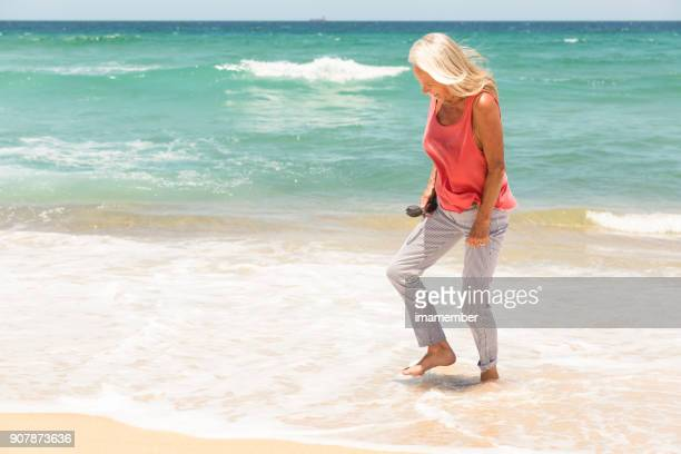 Happy senior woman on the beach, background, copy space