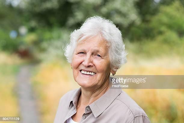 Glückliche senior Frau im Freien, ein Blick in die Kamera
