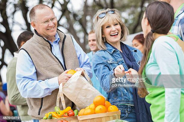 Happy senior woman paying for produce at local farmers market
