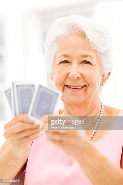 glückliche senior frau spielen karten - bridge card game stock-fotos und bilder