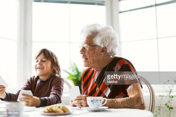 Happy senior woman playing cards with great grandson at home