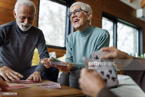 happy senior woman playing cards with her friends at home. - dar cartas imagens e fotografias de stock