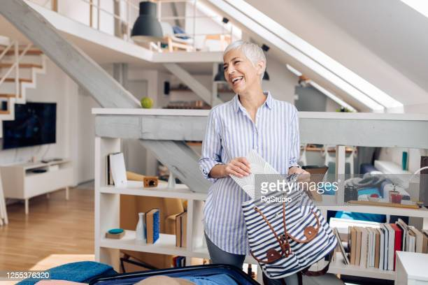 happy senior woman preparing to go on vacation - open backpack stock pictures, royalty-free photos & images