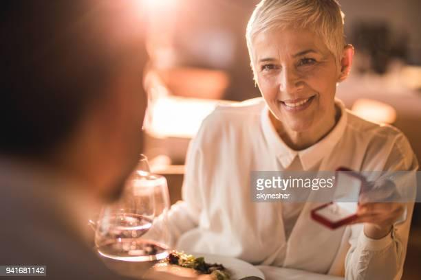 glückliche senior frau zu ihrem freund in einem restaurant vorschlagen. - anniversary stock-fotos und bilder