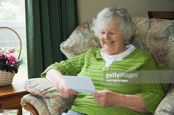 happy senior woman reading a letter - bericht stockfoto's en -beelden