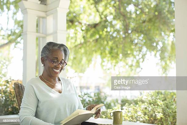 Happy senior woman reading book on porch
