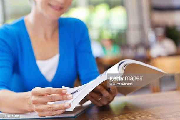 Happy senior woman reading continuing education in library
