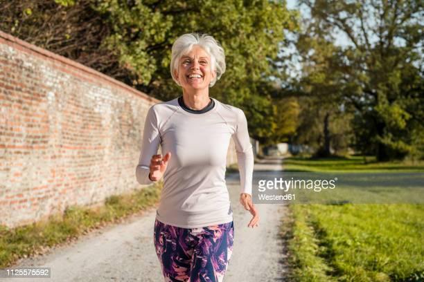 happy senior woman running along brick wall in a park - rennen körperliche aktivität stock-fotos und bilder