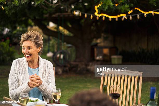 Happy senior woman sitting at table in yard