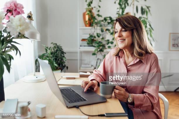 feliz mulher idosa sentada em seu home office e usando seu laptop computador - computer - fotografias e filmes do acervo