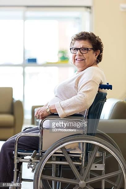 Happy senior woman sitting in wheelchair