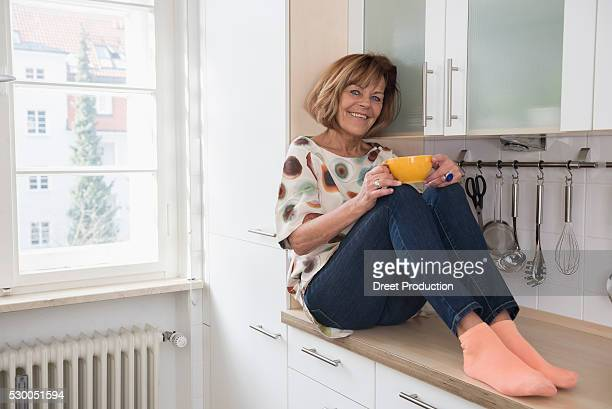 Happy senior woman sitting on kitchen slab and drinking tea, Munich, Bavaria, Germany