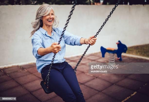 Happy senior woman sitting on playground swing and enjoying retirement