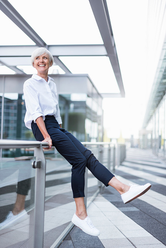 Happy senior woman sitting on railing in the city looking around - gettyimageskorea