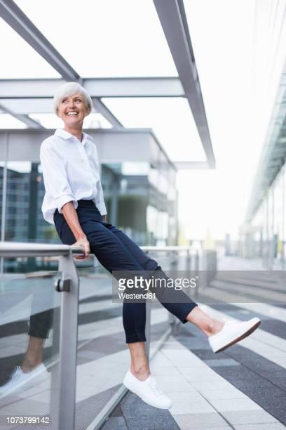 happy senior woman sitting on railing in the city looking around - geländer stock-fotos und bilder