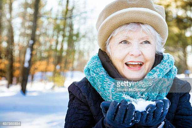 happy senior woman smiling preparing snowball - january stock pictures, royalty-free photos & images