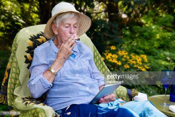 happy senior woman smoking marijuana joint as cannabis medicinal - marijuana joint stock pictures, royalty-free photos & images
