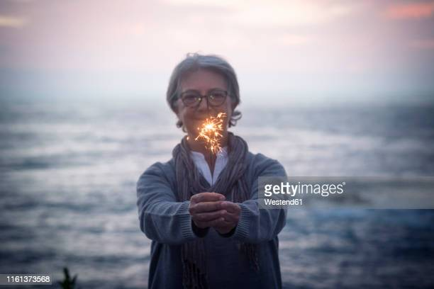 happy senior woman standing in front of the sea by sunset holding sparkler - moody sky stock pictures, royalty-free photos & images