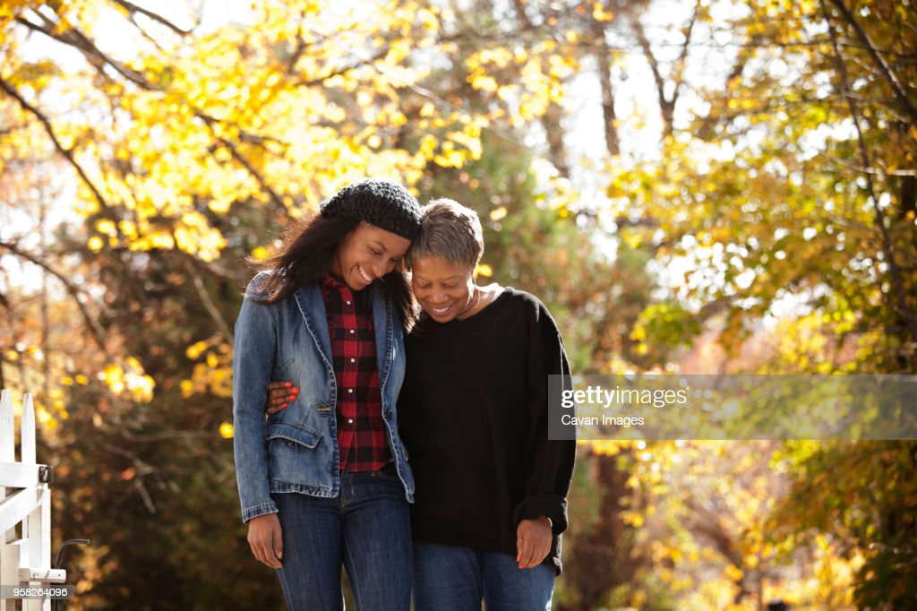 Happy senior woman standing with daughter against trees : Stock Photo