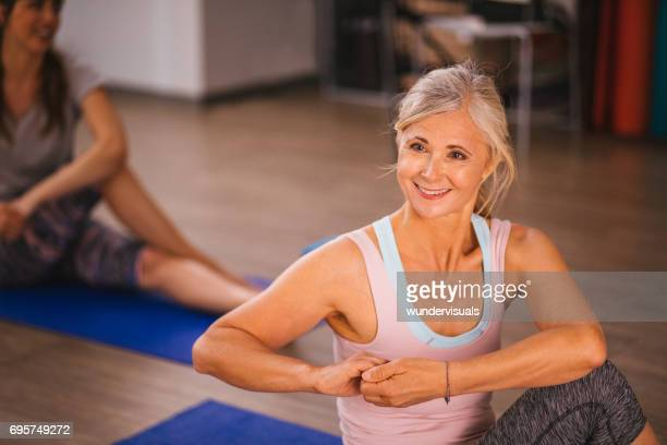 Happy senior woman stretching and keeping fit by doing yoga