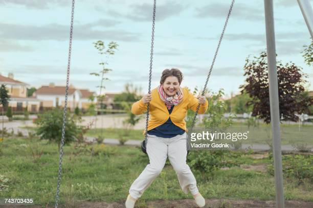 Happy senior woman swinging on swing at playground against sky