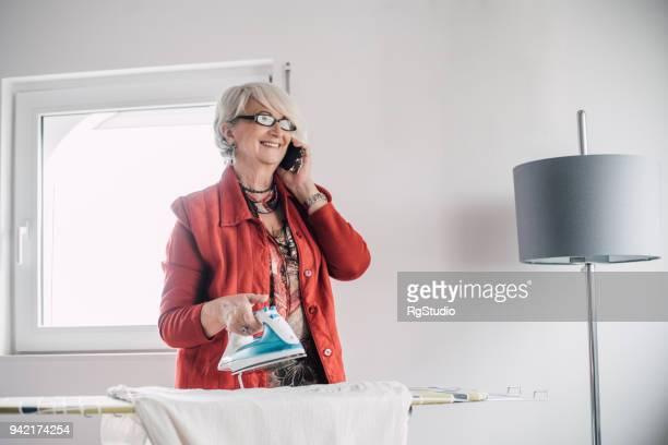 beautiful senior woman sprechen über ein telefon und ein bügeleisen/-brett - unterschicht stereotypen stock-fotos und bilder