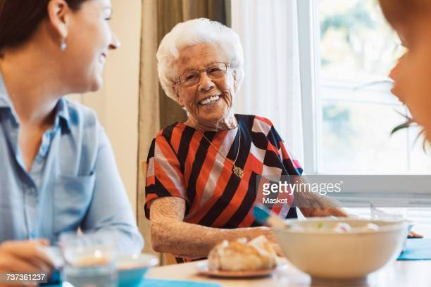 Happy senior woman talking to daughter at dining table