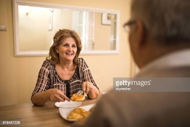 Gelukkig senior vrouw aan haar man te praten tijdens ontbijt thuis.