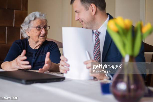 happy senior woman talking to her laywer finishing her paperwork - mortgage stock pictures, royalty-free photos & images