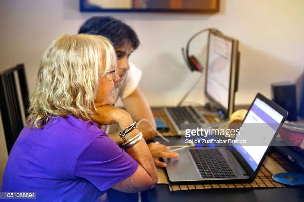Happy senior woman using a laptop with her son in law