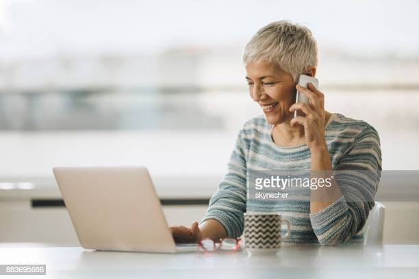 Happy senior woman using laptop and talking on smart phone.